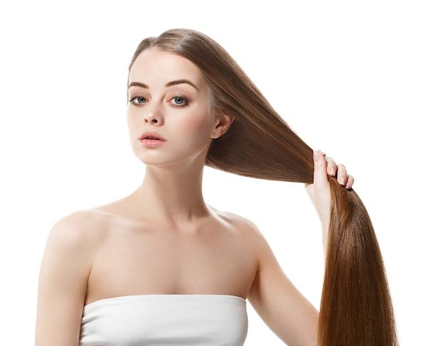Belle femme aux cheveux longs en bonne santé garde les cheveux en main avec la nature maquillage portrait blanc isolé