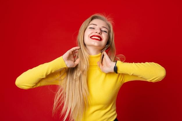 Belle femme aux cheveux longs, debout sur un fond rouge