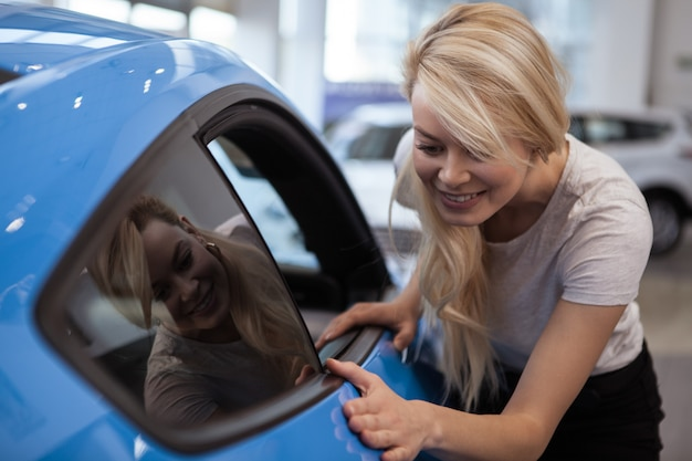 Belle femme aux cheveux longs examinant une voiture en vente dans la salle d'exposition du concessionnaire.