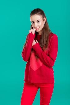 Belle femme aux cheveux longs en pull rouge sur fond vert