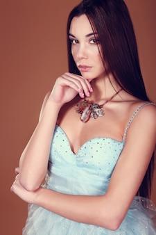 Belle femme aux cheveux noirs et maquillage de soirée. bijoux et beauté.