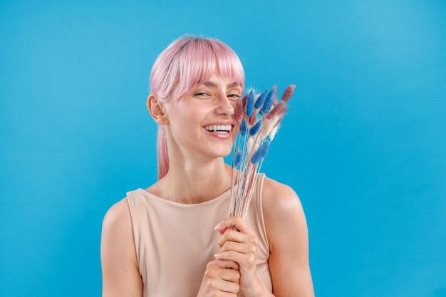 Belle femme aux cheveux roses souriant à la caméra tenant de l'herbe de la pampa séchée dans sa main posant sur