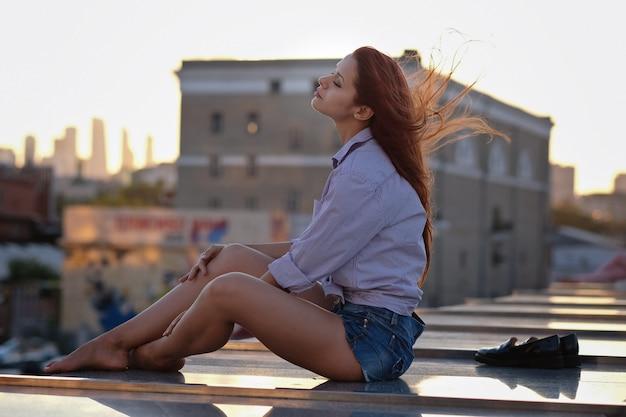 Belle femme aux cheveux rouges assis sur un toit ou un pont