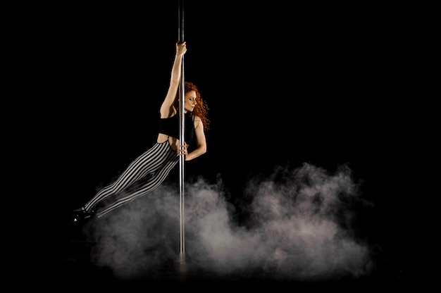 Belle femme aux cheveux rouges effectuant la pole dance