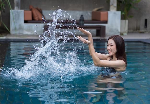 Belle Femme Aux éclaboussures D'eau Dans La Piscine Photo Premium