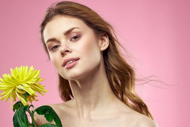 Belle femme aux épaules nues et une fleur jaune dans ses mains sur une rose