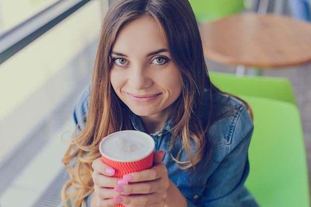 Belle femme aux grands yeux et charmant sourire tenant une tasse de délicieux café avec de la mousse. elle a une conversation avec un ami dans un café. gros plan photo