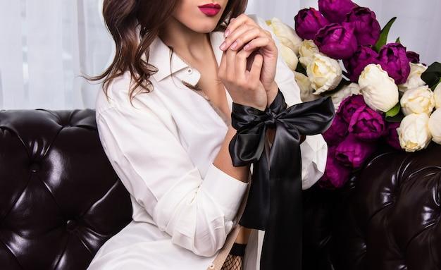 Belle femme aux lèvres brillantes et ruban de soie attaché avec ses mains
