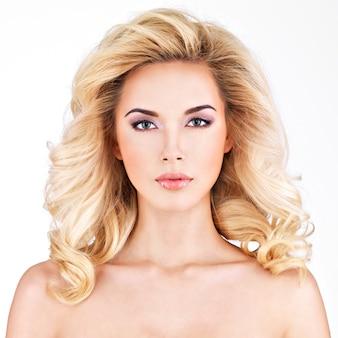Belle femme aux longs cheveux blonds bouclés.isolé sur blanc