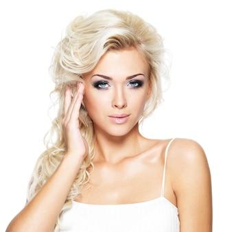 Belle femme aux longs cheveux blonds bouclés. portrait de mannequin avec un maquillage lumineux. isolé sur blanc