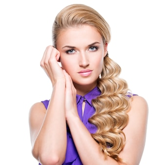 Belle femme aux longs cheveux bouclés blonds et main près du visage - isolé sur un mur blanc.