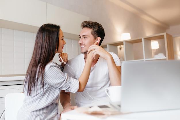 Belle femme aux longs cheveux noirs écoutant la chanson préférée avec son petit ami en week-end