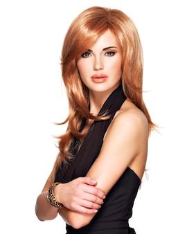 Belle femme aux longs cheveux roux tout droit dans une robe noire. mannequin posant. isolé sur blanc