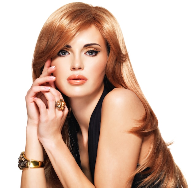 Belle femme aux longs cheveux roux tout droit dans une robe noire touchant son visage. mannequin posant. isolé sur blanc