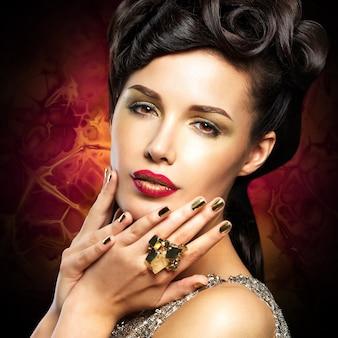 Belle femme aux ongles dorés et aux lèvres rouge vif