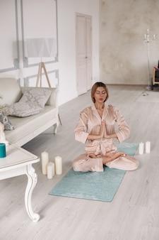 Belle femme aux yeux fermés assise sur le tapis dans la chambre à la maison en position du lotus. concept de mode de vie sain. remise en forme du matin