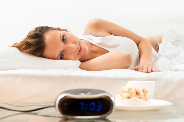 Belle femme ayant un gâteau et un café au lit