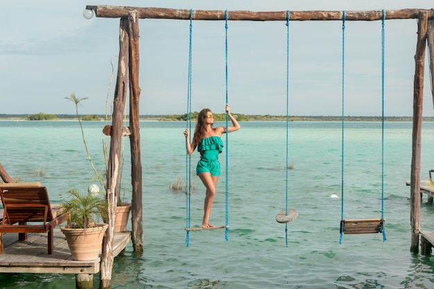 Belle femme sur les balançoires qui au-dessus d'une eau