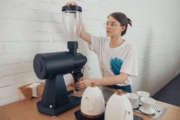 Belle femme barista à l'aide d'une machine à café professionnelle à la cafétéria