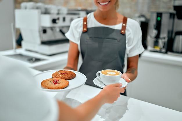 Belle femme barista donnant une tasse de café ou de cappuccino et une assiette de biscuits à un client dans un café.