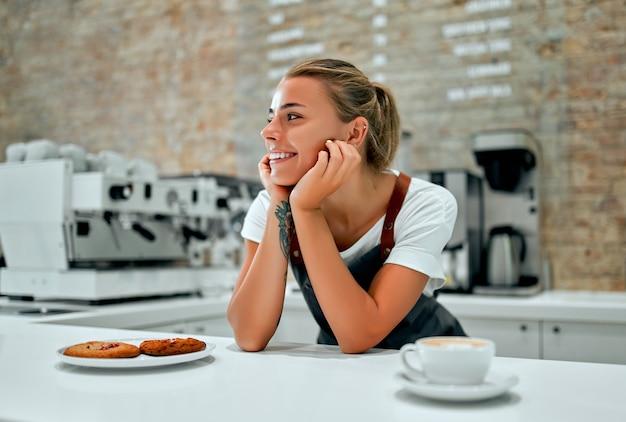 Belle femme barista prépare une tasse de café ou de cappuccino et une assiette de biscuits pour un client dans un café.