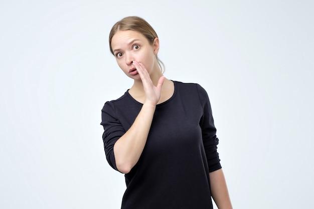 Belle femme bavarde habillée en tshirt noir dit secret