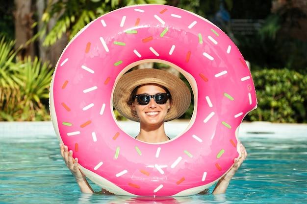 Belle femme avec beignet gonflable dans la piscine