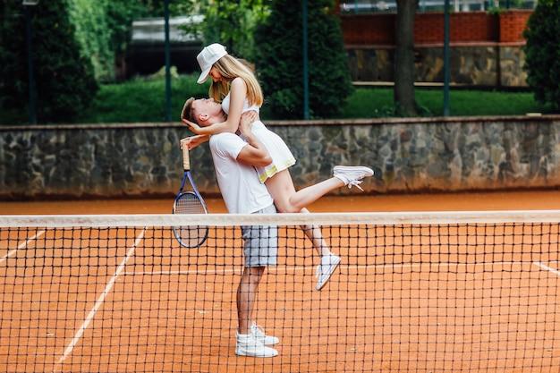 Belle femme et bel homme après jouent au tennis.