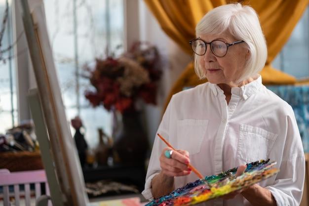 Belle femme. belle femme à la retraite portant des lunettes tenant une palette de couleurs et un pinceau