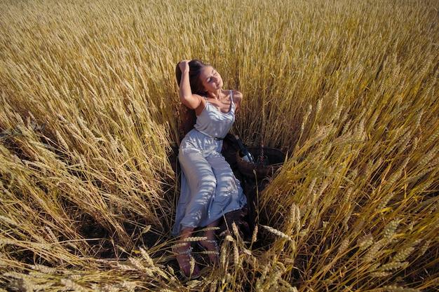 Belle femme belle robe en argent sur un pique-nique sur un champ de seigle, panier avec du vin et des verres
