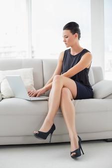 Belle femme bien habillée à l'aide d'un ordinateur portable sur le canapé