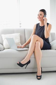 Belle femme bien habillée en utilisant un ordinateur portable et un téléphone portable sur le canapé