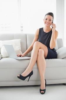 Belle femme bien habillée en utilisant un ordinateur portable et un téléphone portable