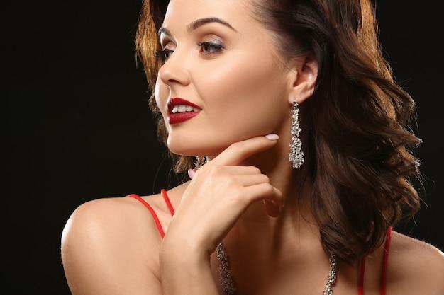Belle femme avec des bijoux élégants sur fond noir
