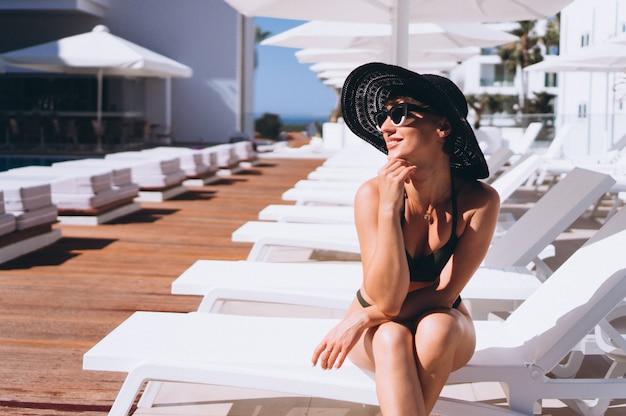 Belle femme en bikini au bord de la piscine