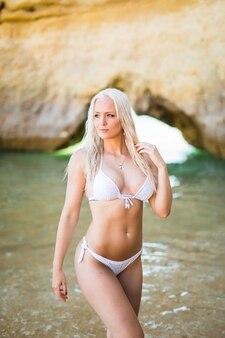 Belle femme en bikini. fille jeune et sportive posant sur une plage en été
