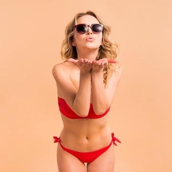 Belle femme en bikini rouge envoie air kiss