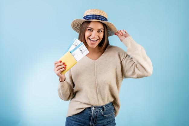 Belle femme avec des billets d'avion dans le passeport et le chapeau de voyage isolé sur bleu