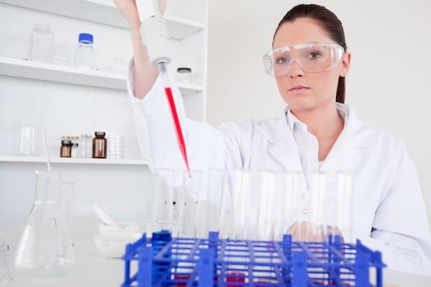 Belle femme biologiste tenant une pipette manuelle avec un échantillon de tubes à essai