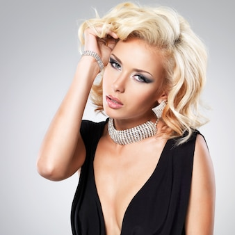 Belle femme blanche avec une coiffure frisée posant au studio