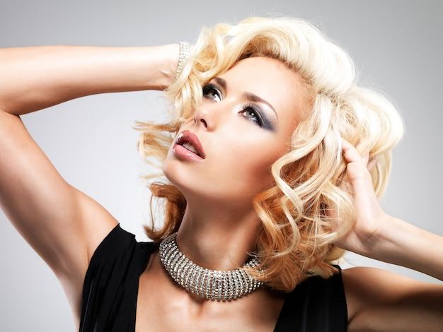 Belle femme blanche avec une coiffure frisée posant