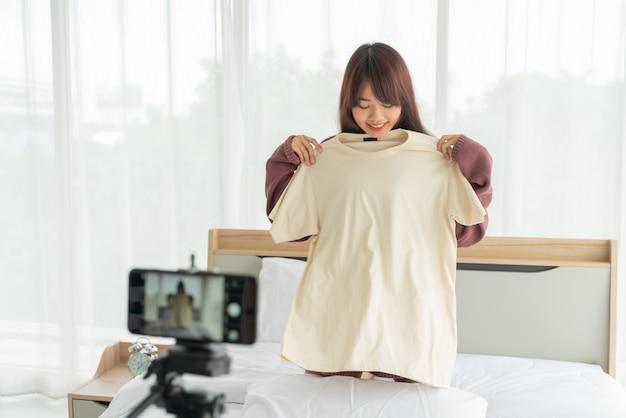 Belle Femme Blogueuse Asiatique Montrant Des Vêtements Sur La Caméra Pour Enregistrer Une Vidéo Vlog En Direct Dans Sa Boutique Photo Premium