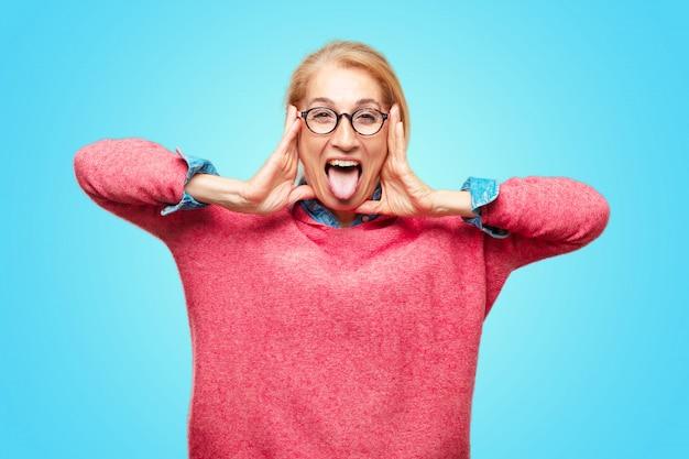 Belle femme blonde adulte blague, sortir la langue avec une expression drôle, idiot et ludique,