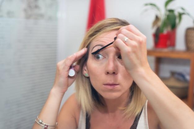 Belle femme blonde appliquant le mascara sur ses cils
