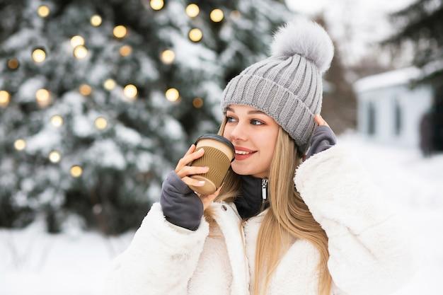Belle femme blonde appréciant le café au parc d'hiver. espace libre