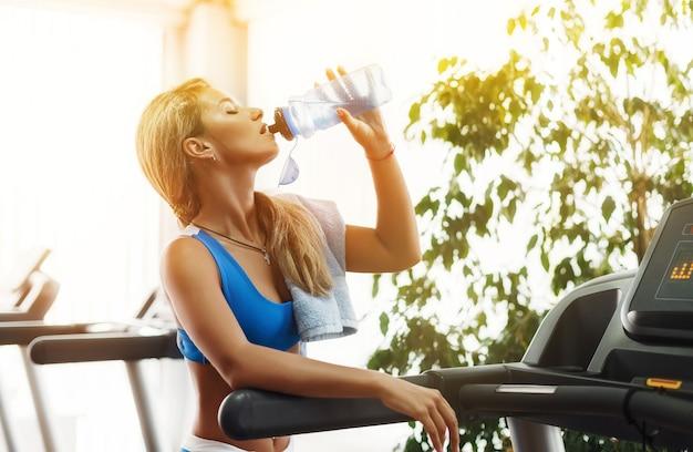 Belle femme blonde athlétique boit de l'eau sur un tapis roulant dans le gymnase.