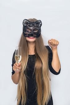 Belle femme blonde au masque de carnaval en studio