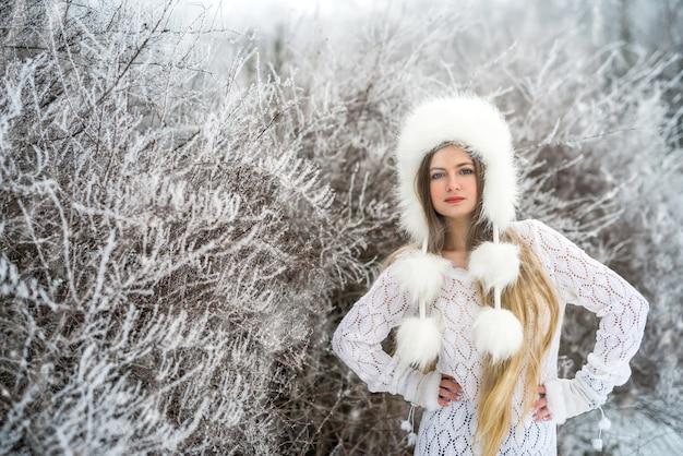 Belle femme blonde aux cheveux longs dans le parc d'hiver