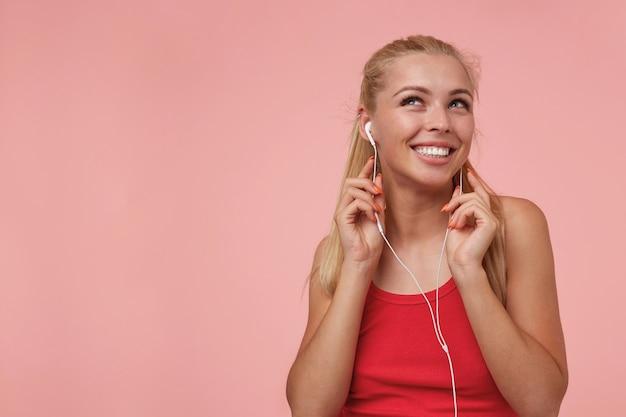 Belle femme blonde aux cheveux longs avec des écouteurs écoutant de la musique préférée, souriant joyeusement et regardant vers le haut