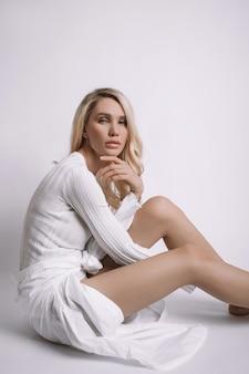 Belle femme blonde aux cheveux longs est assise sur le sol. fille maigre avec de longues jambes
